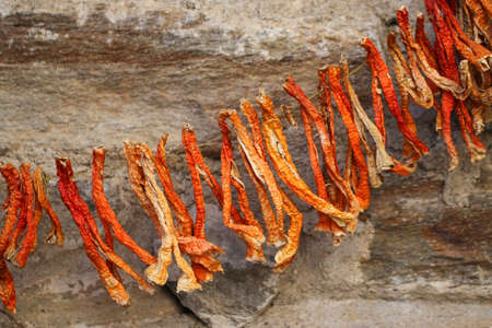 chili peppers: Dried red chili peppers on a stone wall.