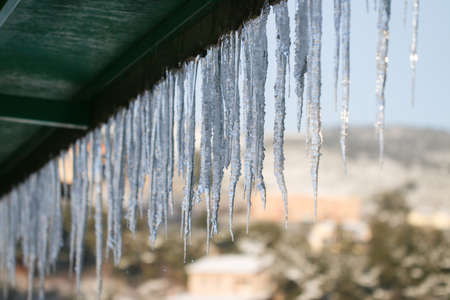 gutter: Winter season scene. Icicles on the roof. cold weather concept. Frozen icy pipe waterspout down.