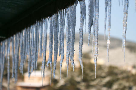 Winter season scene. Icicles on the roof. cold weather concept. Frozen icy pipe waterspout down.