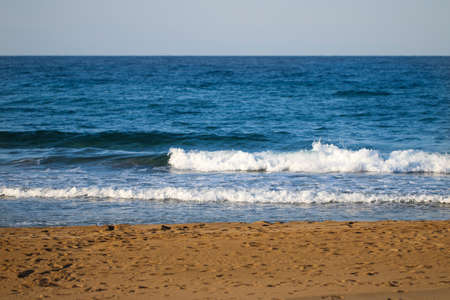 see: Clear blue sea water with waves and beach.