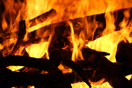 Closeup of a large fire. Wooden planks to the fire. The fire is lit in the night.