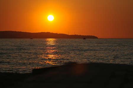 Sun setting over the ocean and tropical beach.