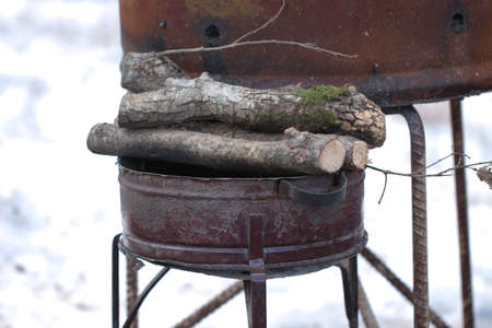Wood in metal brazier. Places are covered with snow.