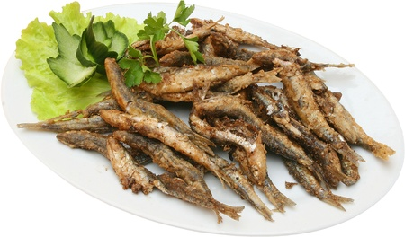 sprats: fried sprats with lettuce on plate isolated  Stock Photo