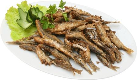 pescado frito: sardinas fritas con lechuga en la placa aislada