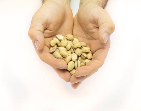 hand holding pistachio nut isolated on white background
