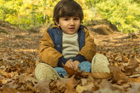 Little boy, playing in the rain in autumn park, leaves around him