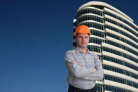 Architect in hard-hat against modern building Stock Photo