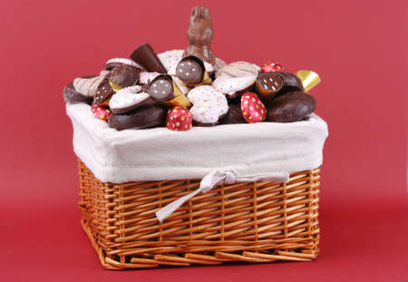 bunny xmas: Easter basket with sweets on red backgrond Stock Photo