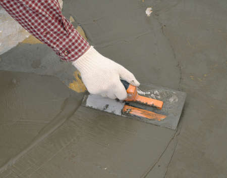 materials: Construction worker spreading wet concrete Stock Photo