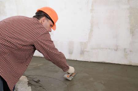Construction worker spreading wet concrete Stock Photo