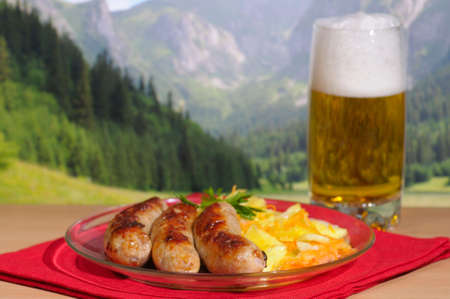 Beer and sausages against mountains Imagens