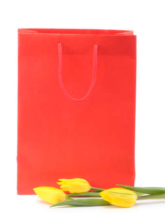 Yellow tulips with a gift bag isolated on white background photo