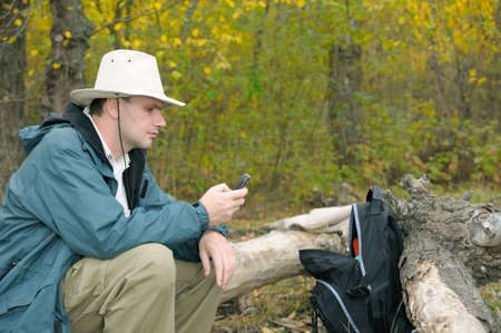 Man checking SMS with a mobile phone in autumn forest photo
