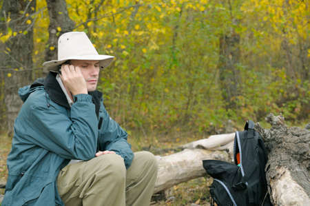 Man  with a mobile phone in autumn forest photo