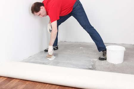 gluing: man puts glue for a linoleum flooring