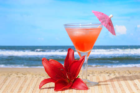 Glass of Cocktail with lily flower at the Beach photo