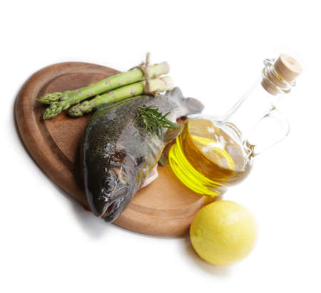 Raw trout with lemon, asparagus, and olive oil on a wooden cutting board isolated on white photo
