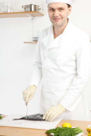 Chef cleaning a fish on white cutting board photo