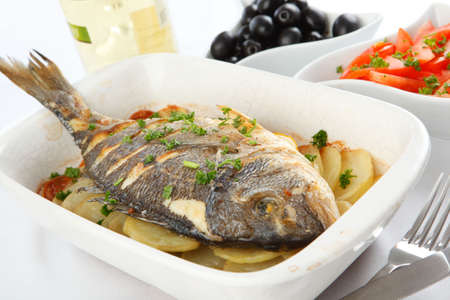 Roasted gilt-head sea bream with vegetables and white wine photo