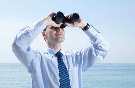 Businessman with binoculars against blue sky