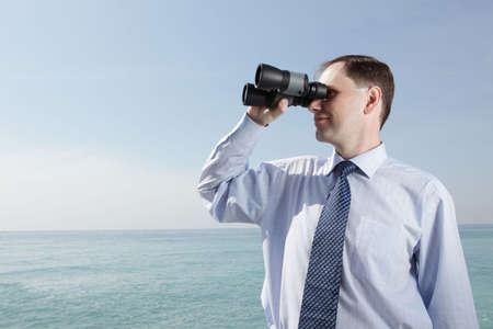Businessman with binoculars against sea background Stock Photo - 4901649