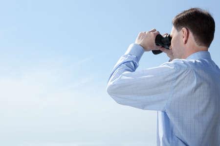 Businessman with binoculars against blue sky Stock Photo - 4901625