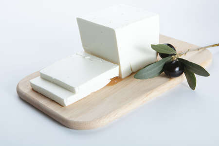 cheese board: Feta cheese with olive on a wooden cutting board