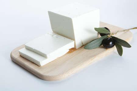 queso de cabra: Queso feta con aceite de oliva en una tabla de cortar de madera Foto de archivo