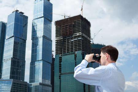 Businessman with binoculars against modern building photo