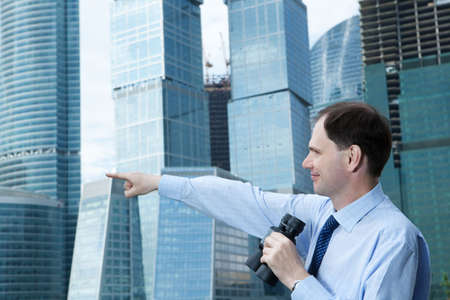Businessman with binoculars against modern building Stock Photo - 4901804
