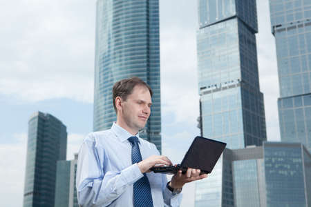 Businessman with laptop against modern building photo