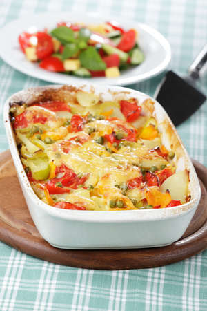 Vegetable baked pudding in white bowl on a wooden board photo
