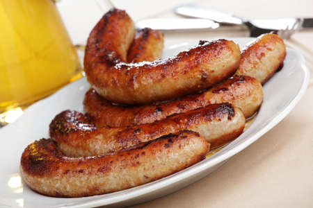 octoberfest: Roasted sausages on white plate and beer Stock Photo
