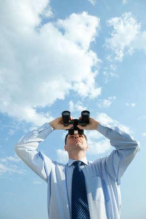 Businessman with binoculars against blue sky Stock Photo - 5124137
