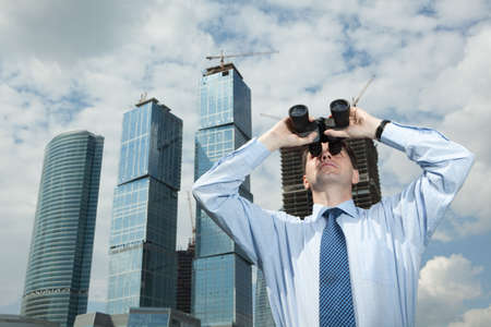Businessman with binoculars against modern buildings photo