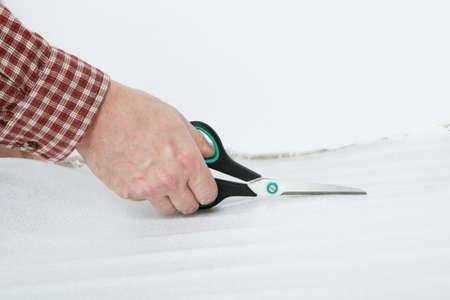 underlay: Mano del hombre con unas tijeras para cortar la base de la instalaci�n de suelos laminados