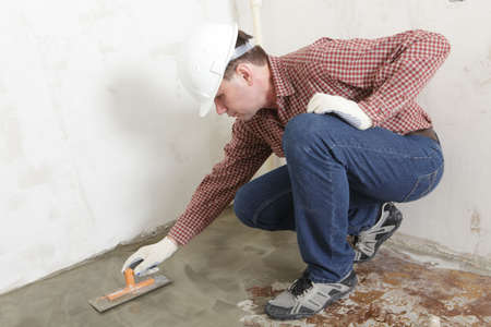 manual job: Construction worker spreading wet concrete Stock Photo