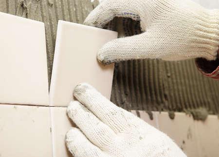 azulejos cocina: El hombre se instala baldosas de cer�mica en una pared Foto de archivo