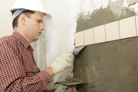 Man installs ceramic tile on a wall photo