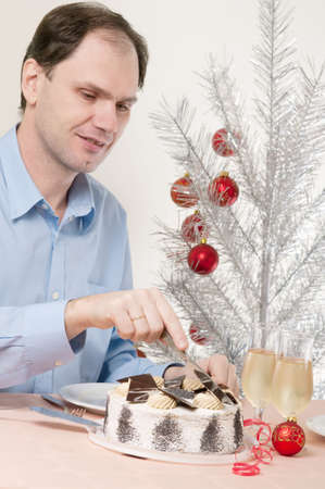 Man cutting the festive cake under Christmas tree Stock Photo - 5500594