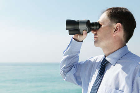 Businessman with binoculars against blue sky Stock Photo - 5500619