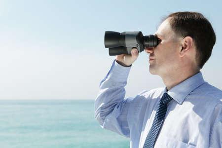 Businessman with binoculars against blue sky photo
