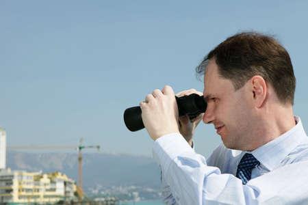 backward: Businessman with binoculars looking backward