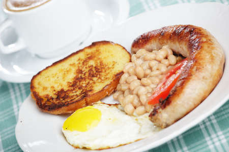 English breakfast with sausage, fried egg, and string bean photo