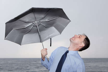 Businessman holding umbrella and looking at sky Stock Photo - 5620218