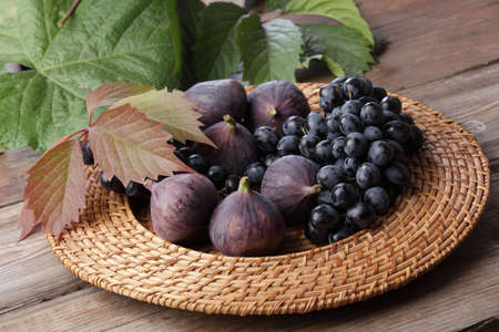 perishable: Figs and grapes in rustic plate Stock Photo