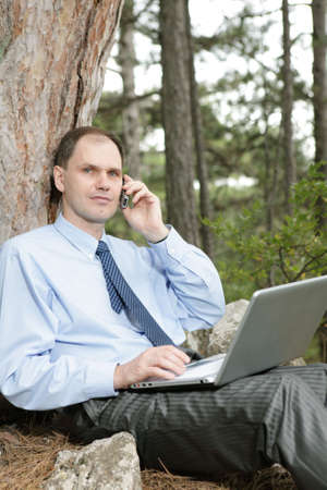 Businessman with laptop and mobile phone in the forest photo