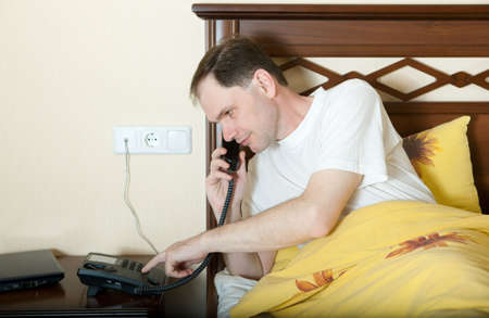 Man in bed in hotel room calling by phone photo