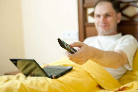 Man in the bed in hotel room with TV remote control photo